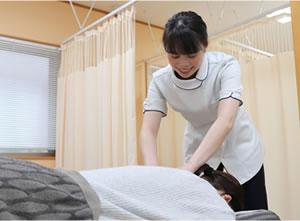 交通事故施術を行う女性施術者
