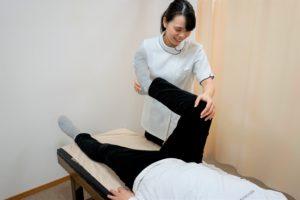 股関節の施術を行う女性施術者
